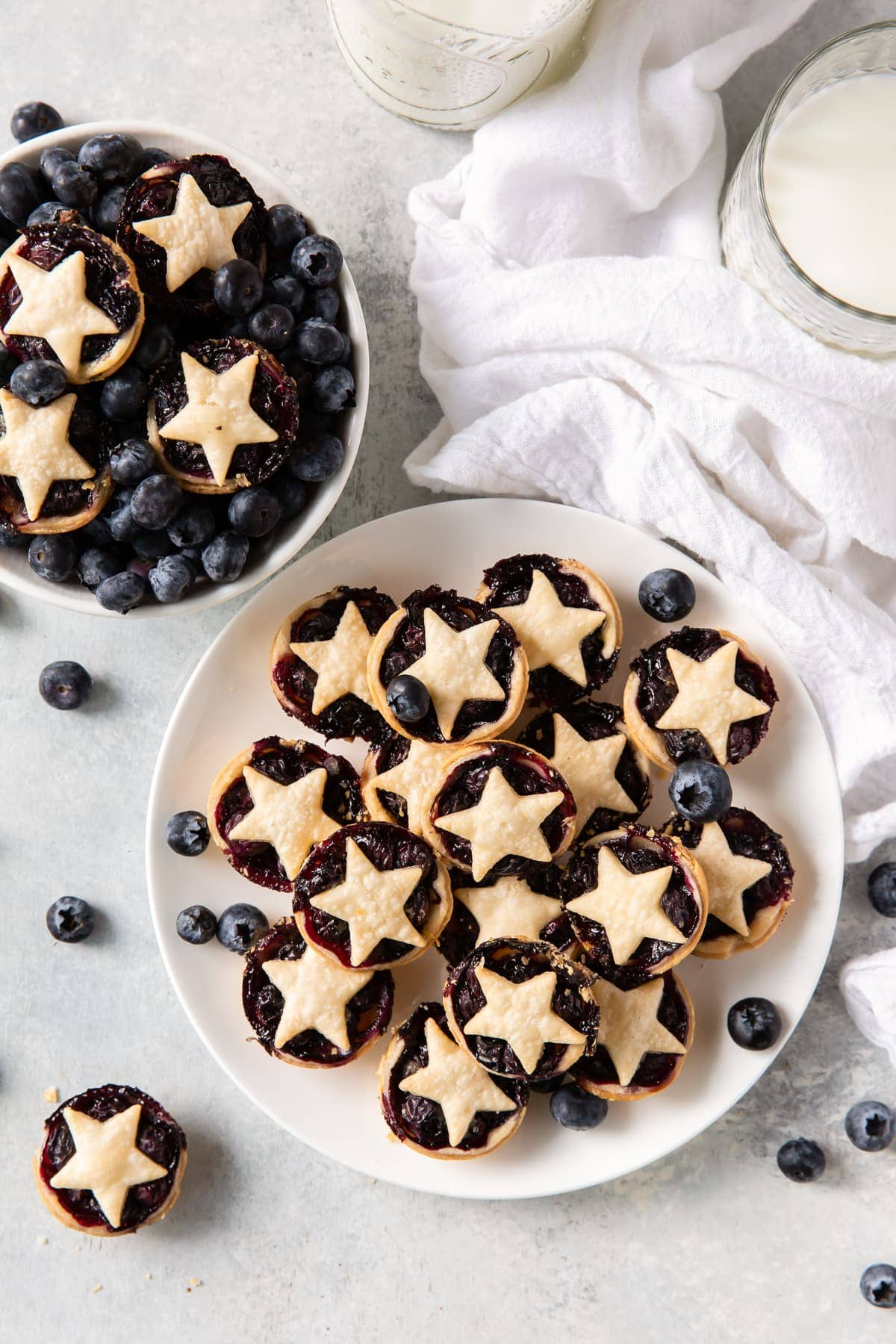 plate of mini blueberry pies next to bowl of blueberries with pies on top