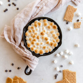 smores dip in small skillet topped with toasted mini marshmallows and pink cloth wrapped around handle