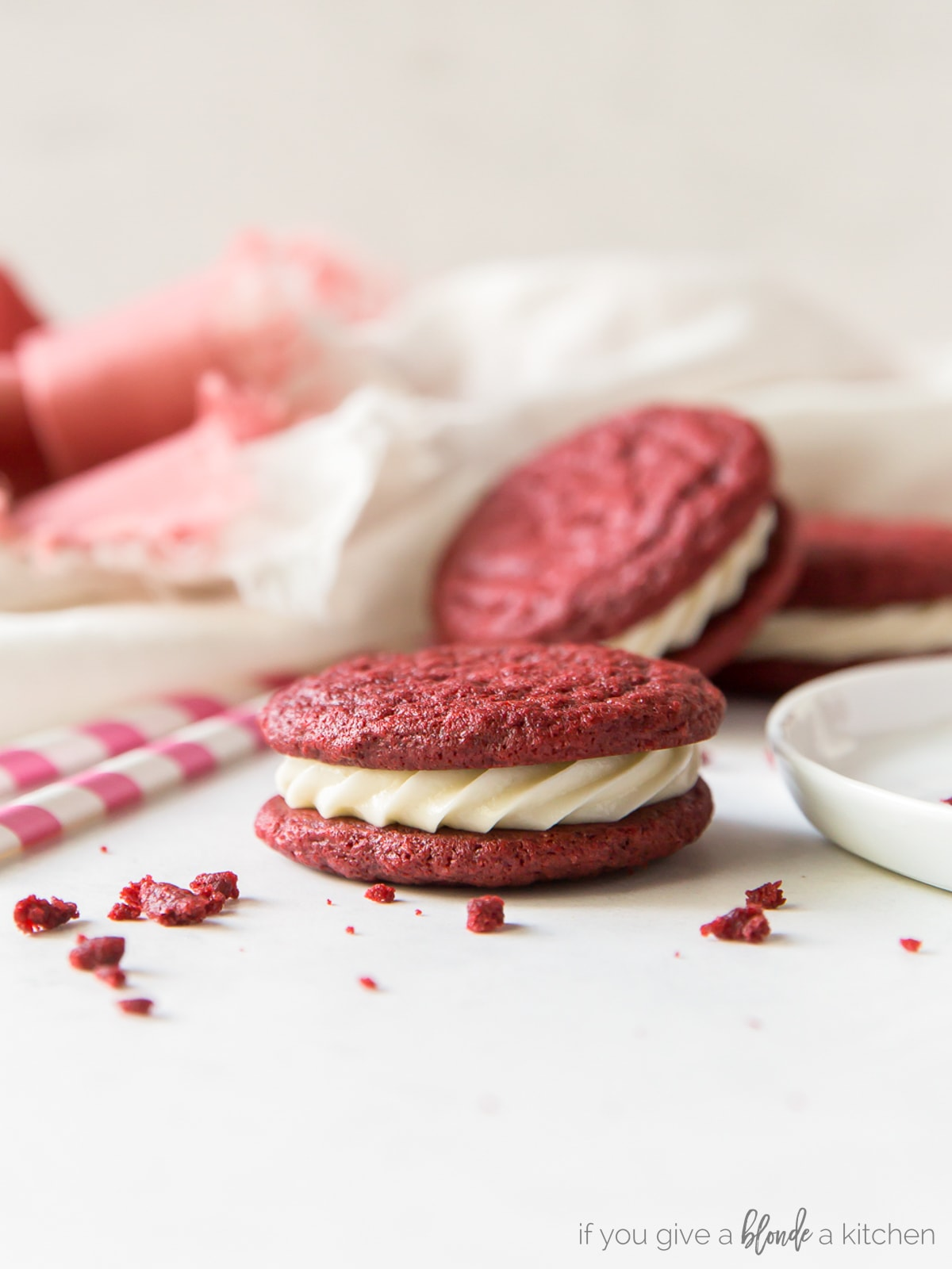 Red velvet sandwich cookies are perfect for Christmas time! Save this recipe for Valentine's Day too.   www.ifyougiveablondeakitchen.com