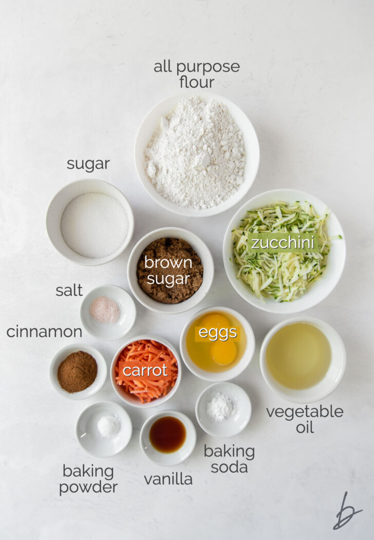 carrot zucchini muffin ingredients in bowls labeled with text