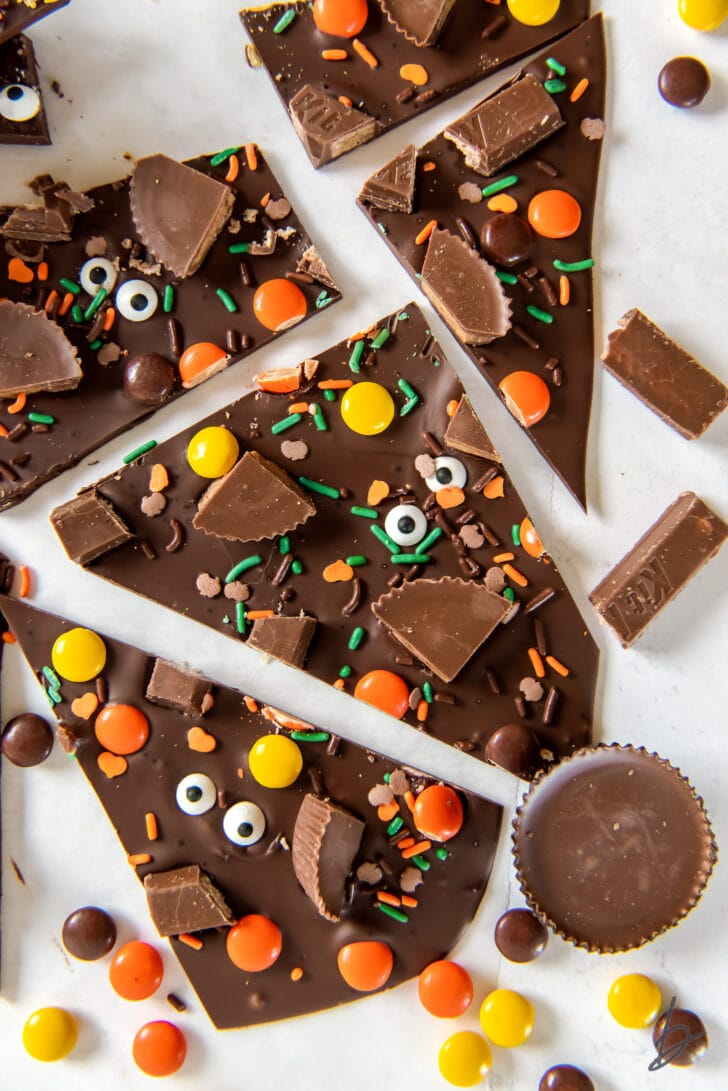 pieces of broken halloween candy bark surrounded by Reese's piece and peanut butter cups