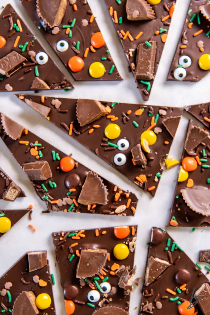 halloween candy bark broken up into triangles with bits of candy and sprinkles on top of the bark