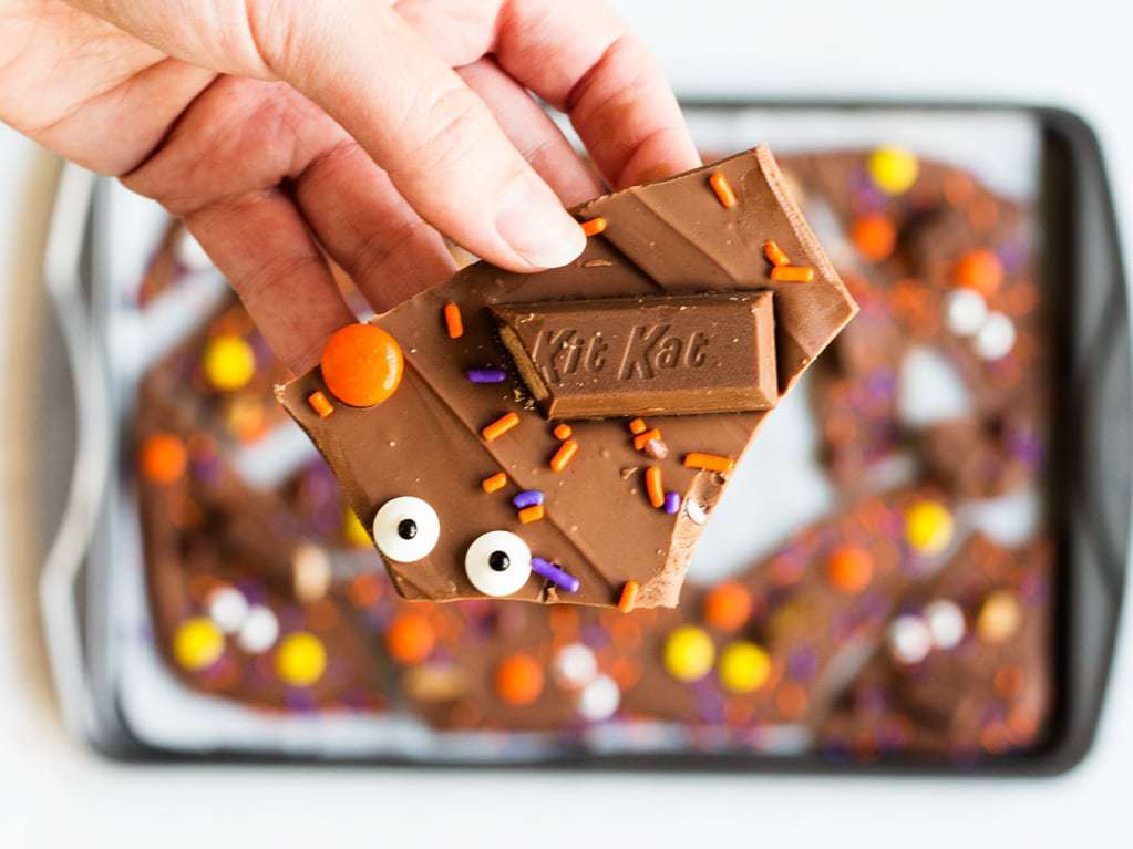 Halloween candy is melted chocolate topped with candy eyes, sprinkles, Kit Kats and Reese's peanut butter cups. | www.ifyougivebalondeakitchen.com