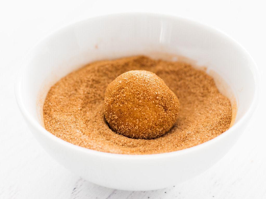 cookie dough ball in small white bowl of cinnamon sugar