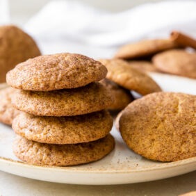 stack of pumpkin snickerdoodles on a white round plate with more cookies next to stack