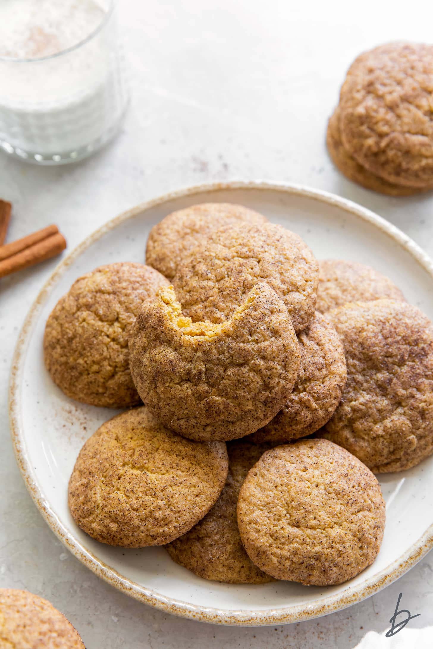 pumpkin snickerdoodles on wire cooling rack and cinnamon sticks
