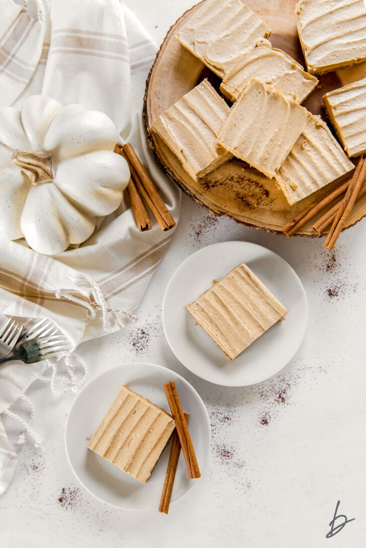 two small white plates with pumpkin cheesecake bars and wood serving tray with more pumpkin cheesecake bars