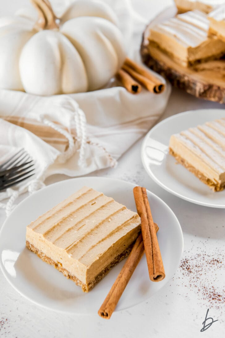 pumpkin cheesecake bar on a white round plate with two cinnamon sticks and a white pumpkin behind plate