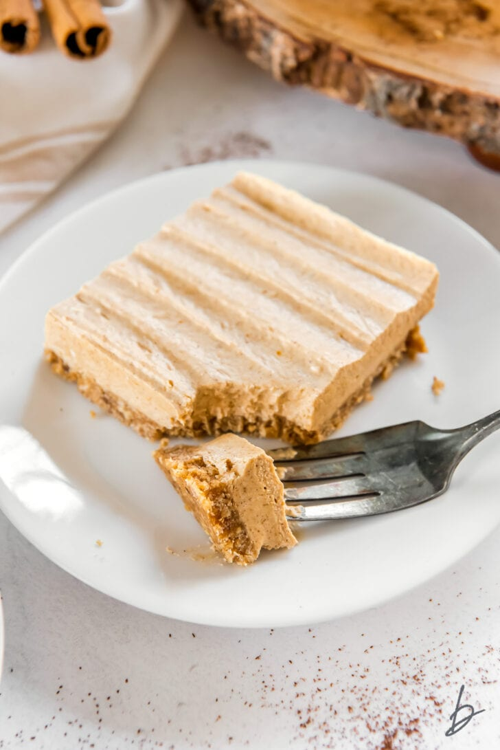 no bake pumpkin cheesecake bar on a white round plate with fork taking bite