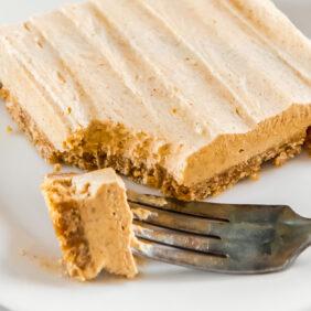 no bake pumpkin cheesecake bar on plate with fork taking bite