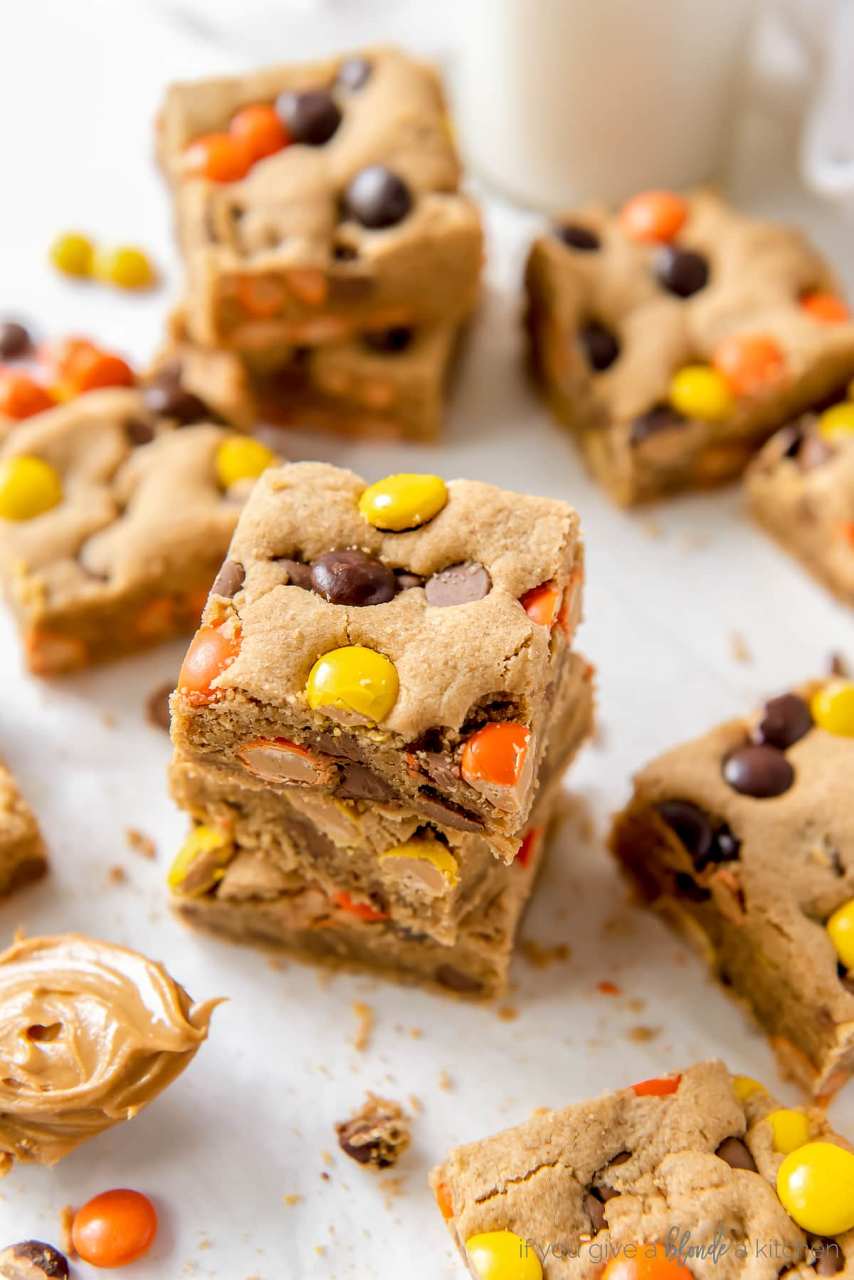 stack of reeses pieces peanut butter blondies on parchment paper next to more blondies
