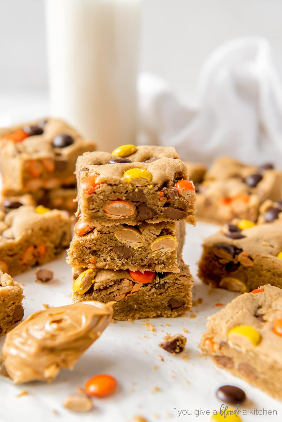 three reeses pieces peanut butter blondies stacked on top of each other