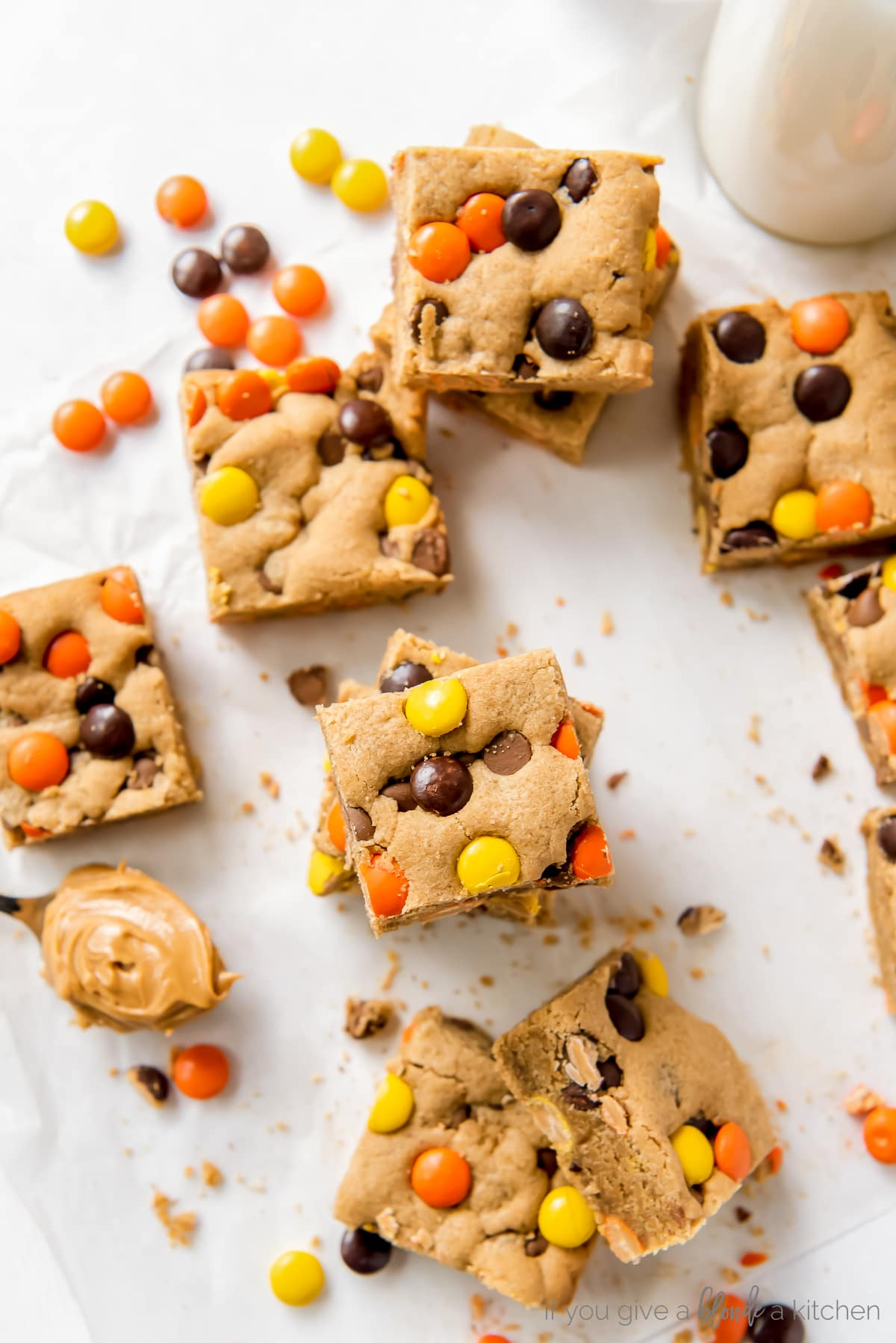 reeses pieces peanut butter blondies on parchment paper next to more reeses pieces candies and spoon of peanut butter