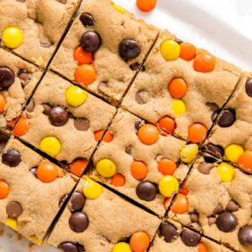 reeses pieces peanut butter blondies cut into squares on parchment paper