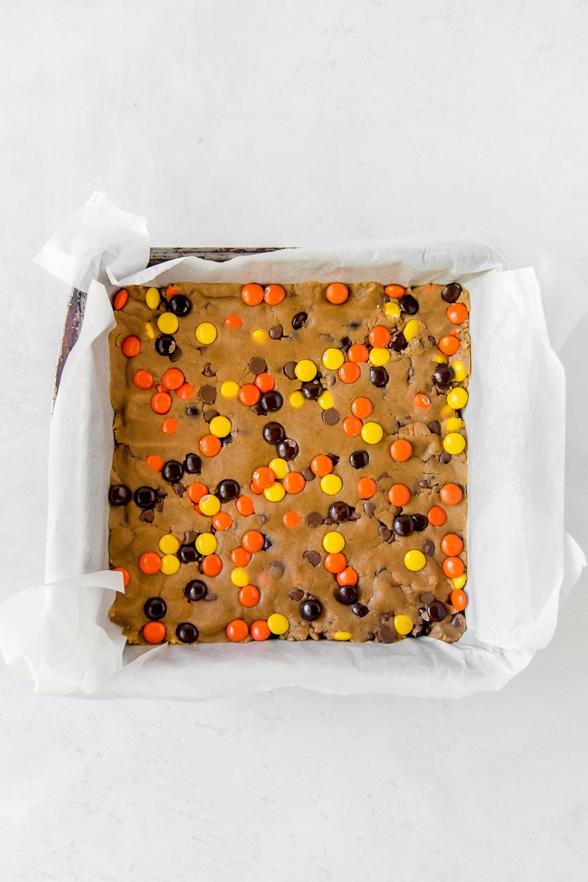 reeses pieces peanut butter blondies dough presses into parchment-lined square baking pan