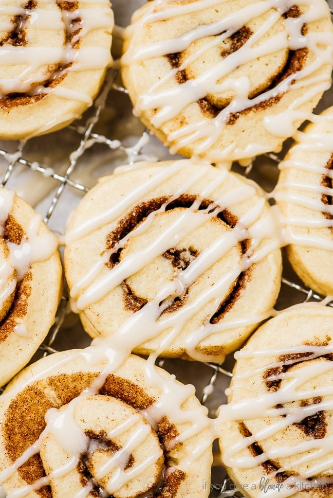cinnamon roll cookies with icing on cooling rack
