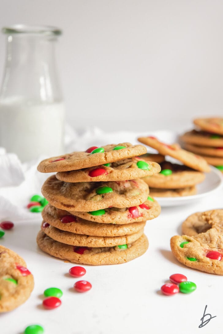 Christmas M&M cookies stacked with red and green M&M candies and glass milk bottle