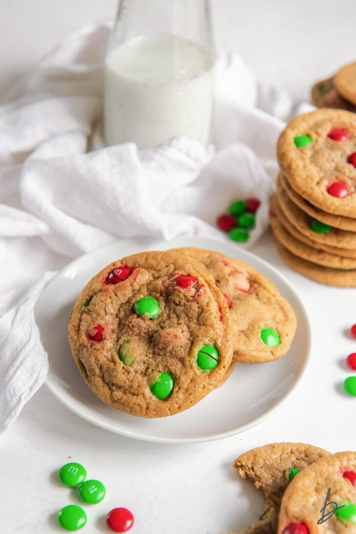 M&M christmas cookies on white round plate next to more cookies and white kitchen cloth