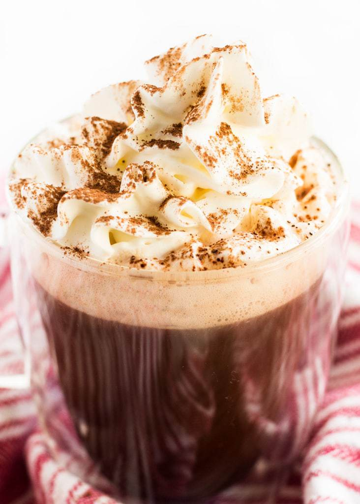 Mocha hot chocolate coffee is topped with whipped cream and a dusting of cocoa to make a festive drink.   www.ifyougiveablondeakitchen.com