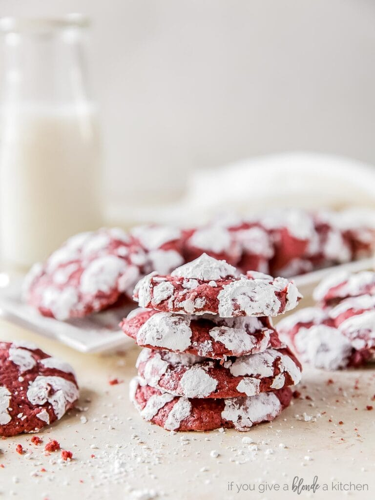 stack of four red velvet crinkle cookies with powdered sugar