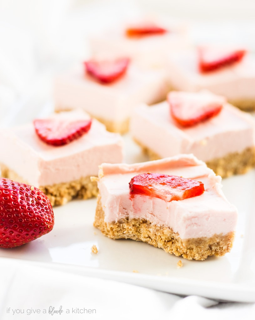 No bake strawberry cheesecake bars have the best graham cracker crust and a deliciously sweet cheesecake filling. It's easy to make for parties! | www.ifyougiveablondeakitchen.com
