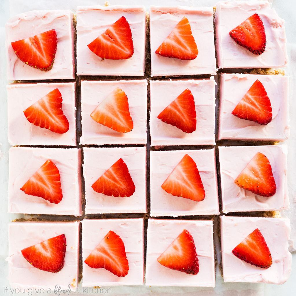 No bake strawberry cheesecake bars are cut into squares for a simple and sweet dessert. Try the recipe for Valentine's Day or Mother's Day. | www.ifyougiveablondeakitchen.com