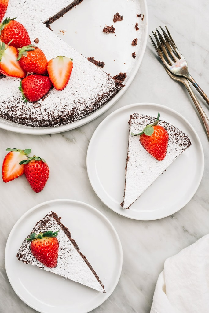 slices of flourless chocolate cake on white round plates with strawberries