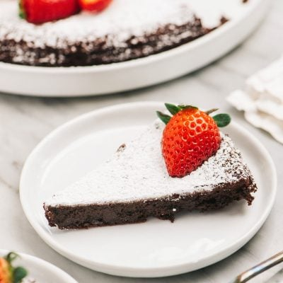 slice of flourless chocolate cake with powdered sugar and strawberry on white round plate