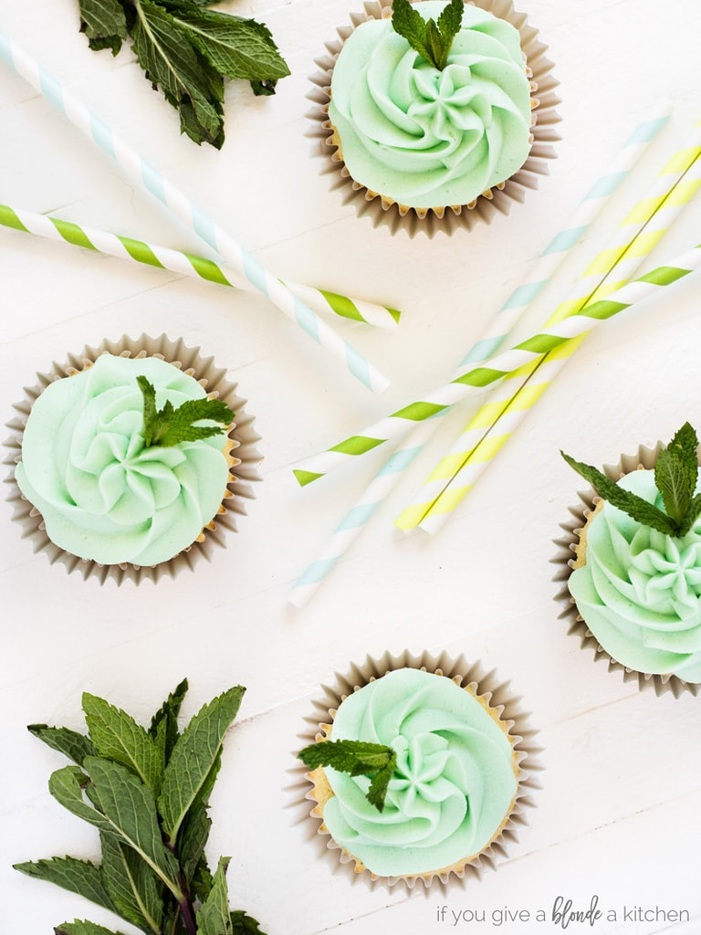 Kentucky Derby Mint Julep Cupcakes overhead shot with green frosting, mint leaves and striped straws