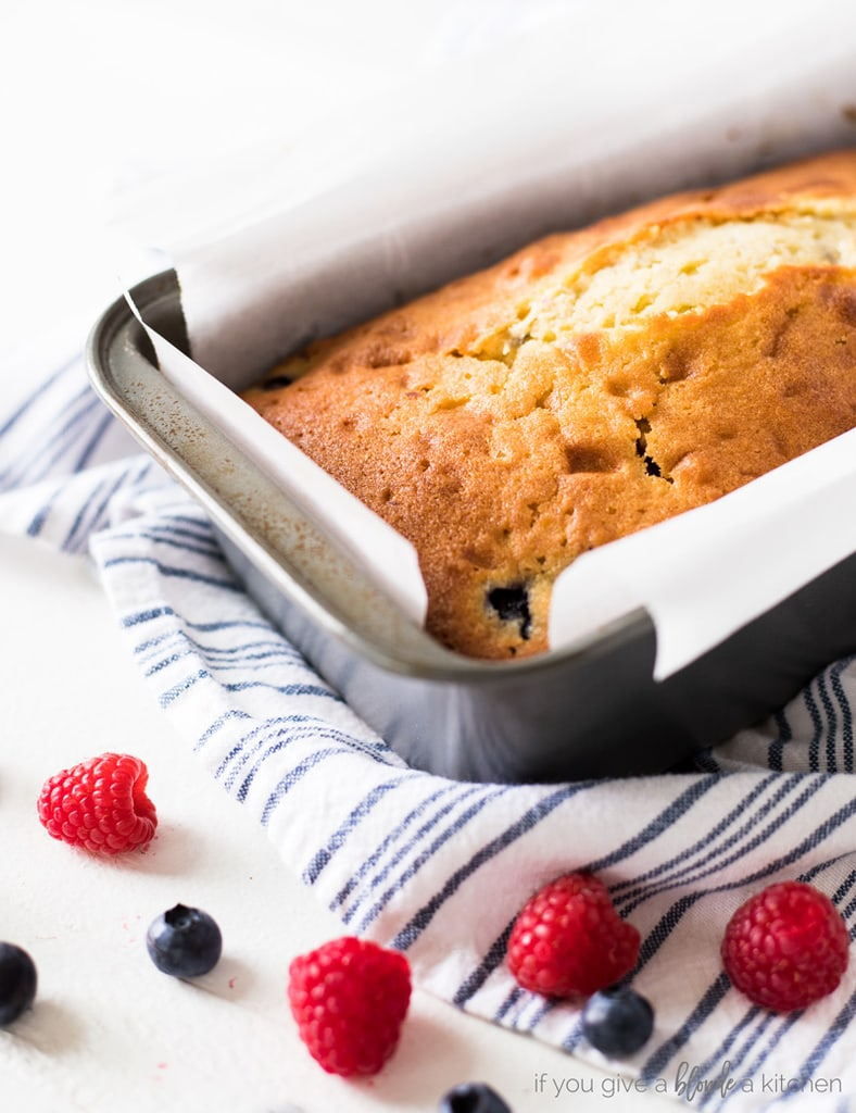 Blueberry raspberry pound cake in baking pan on striped cloth