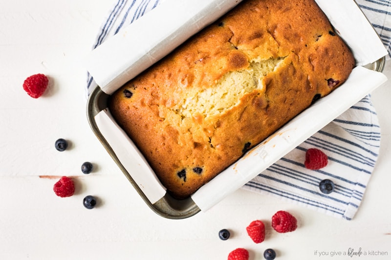 Blueberry raspberry pound cake in pan with parchment paper overhead photo