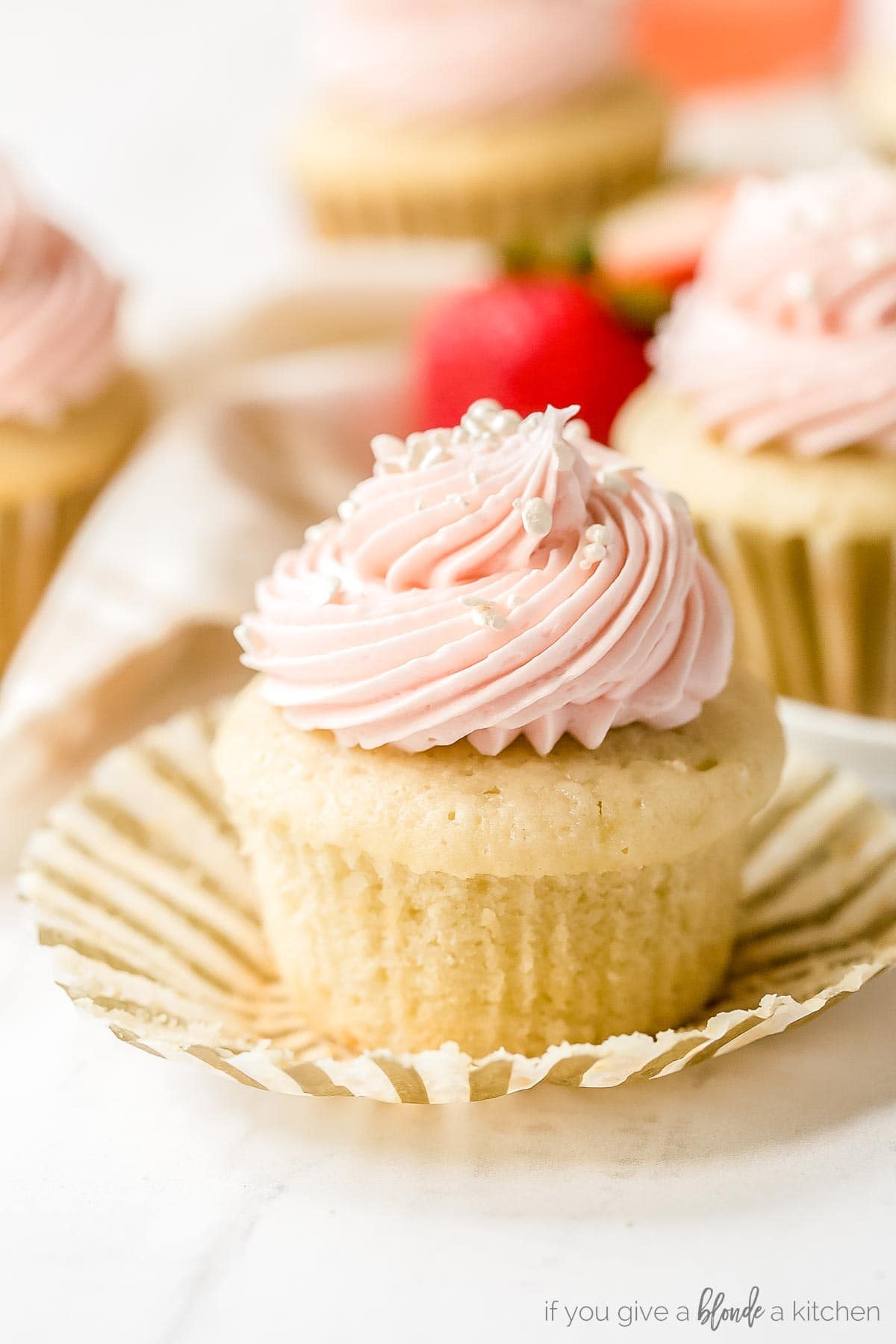 strawberry moscato cupcakes recipe with bite taken out of cupcake sitting on cupcake liner with strawberries
