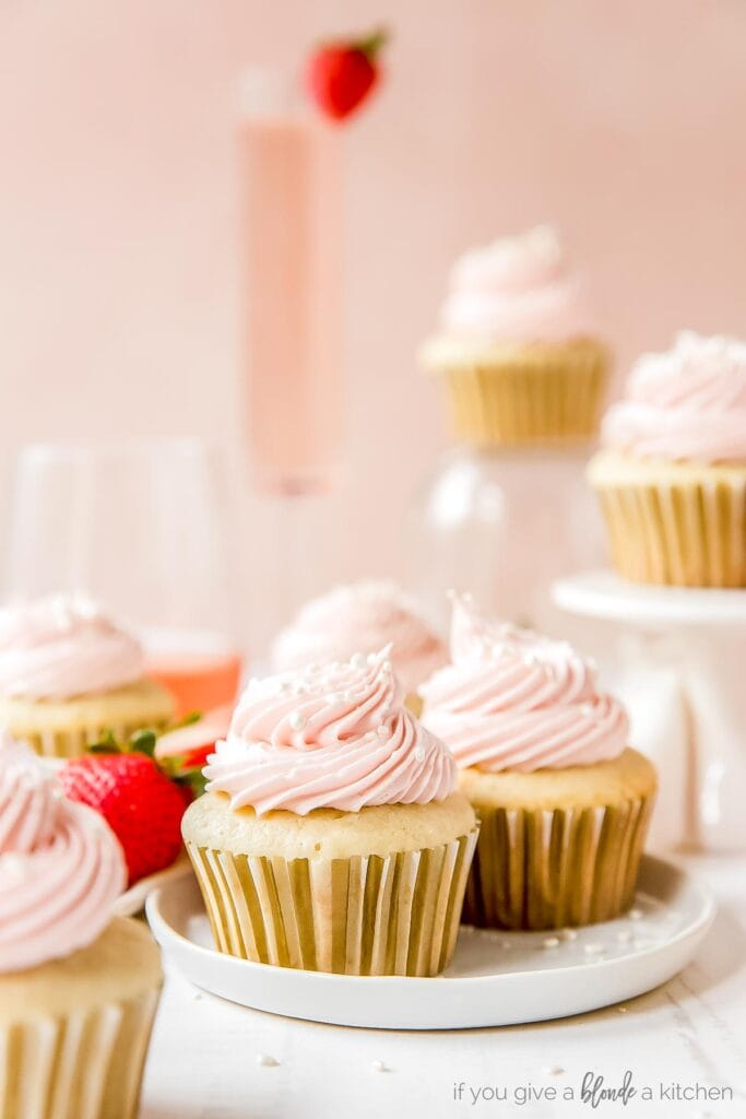 moscato cupcakes with pink frosting on white round plate