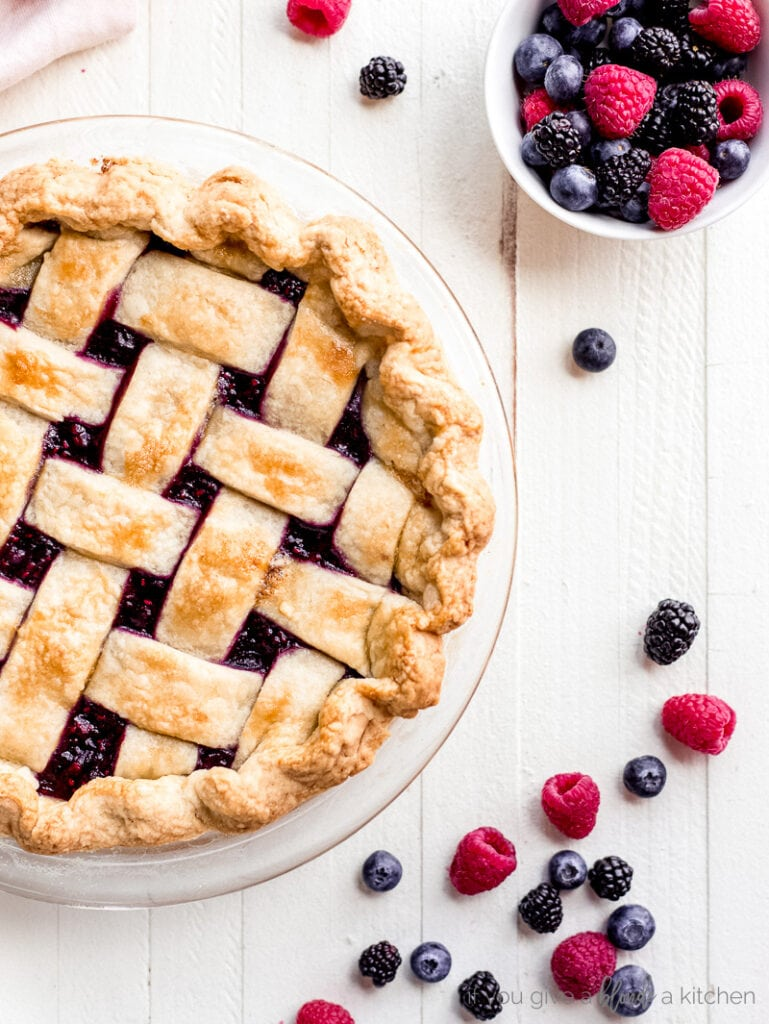 close of up lattice crust pie with berries next to it