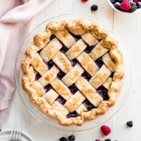 triple berry pie on white wood background. bowl of berries