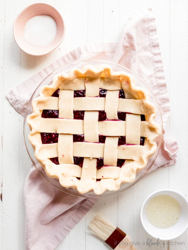 unbaked lattice pie crust with crimped edges. Small pink bowl of sugar. Small white bowl with beaten egg white. Pastry brush.