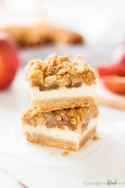 Apple cheesecake bars stacked on top of each other showing layers of shortbread crust, cheesecake, apples and streusel
