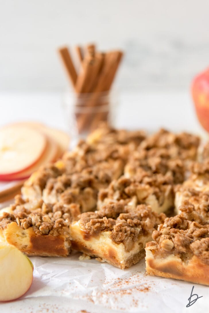 apple cheesecake bars with streusel on parchment paper