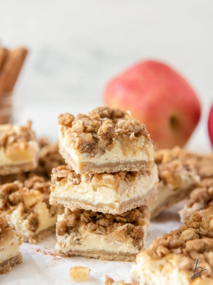 stack of three apple cheesecake bars showing layers of shortbread crust, cheesecake, apples and streusel
