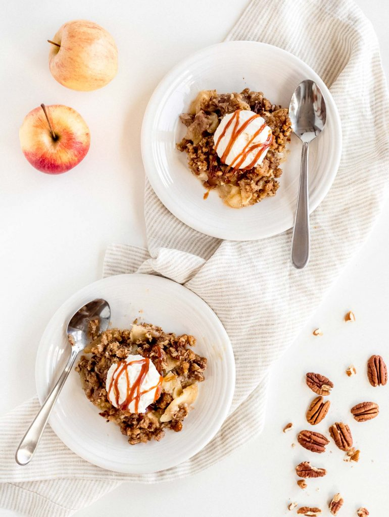 two servings on apple crisp with vanilla ice cream and caramel on round plates