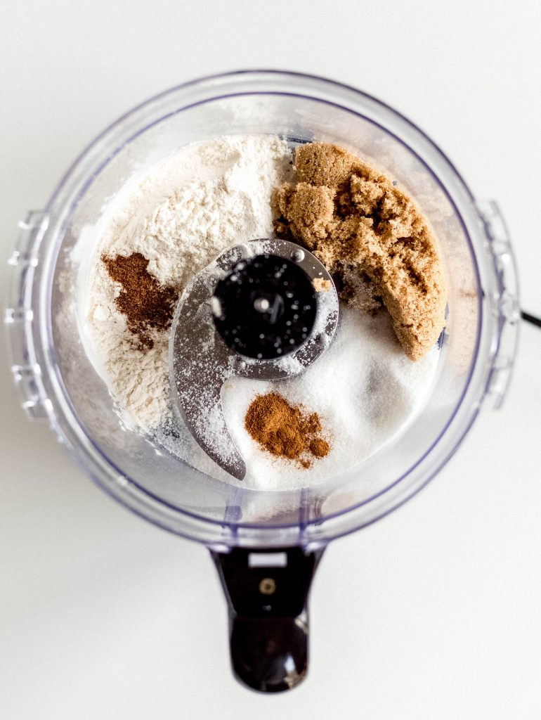 food processor with flour, brown sugar, sugar, cinnamon and nutmeg