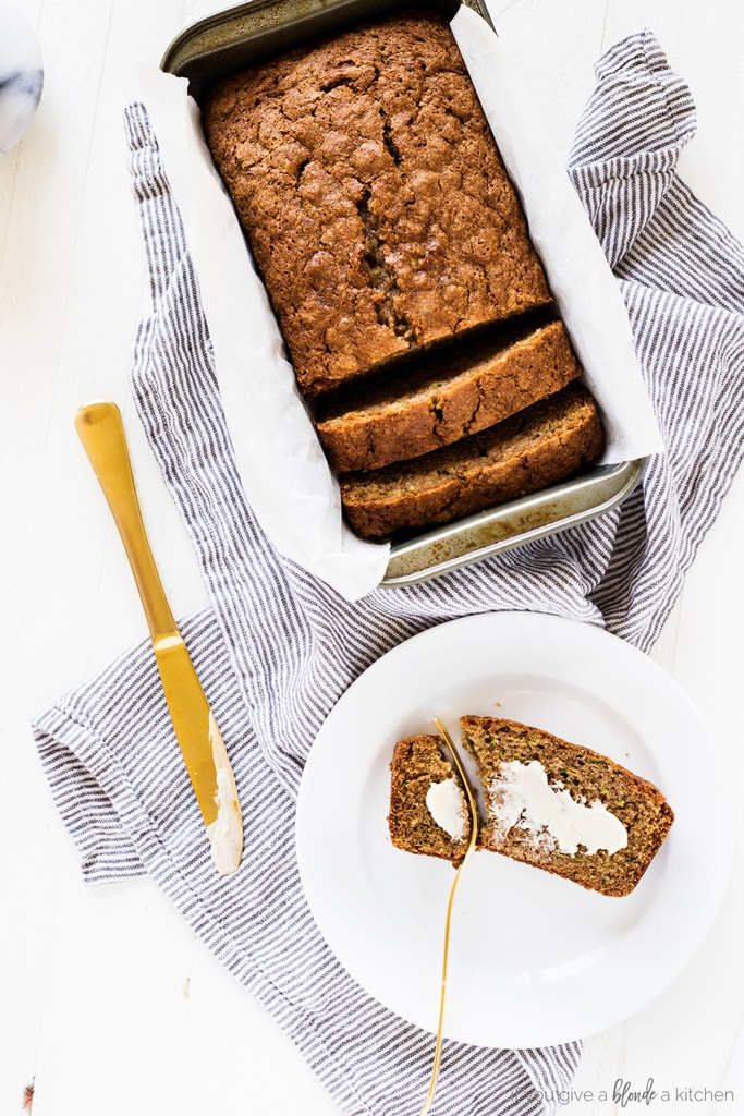 zucchini bread with loaf pan, gold knife, buttered slice, cloth and round white plate