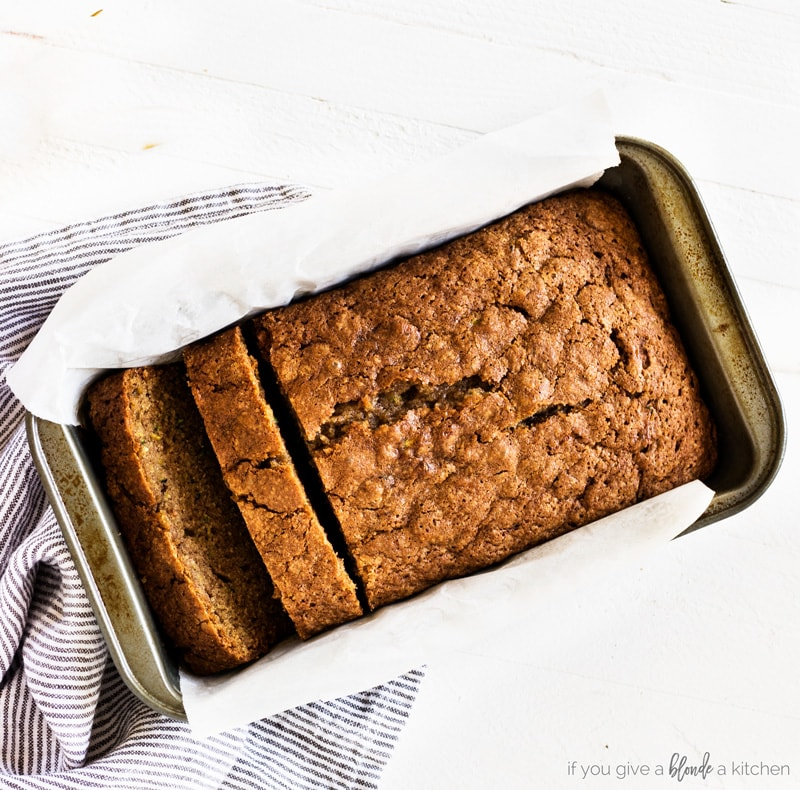 Moist zucchini bread in loaf pan with cloth and parchment paper