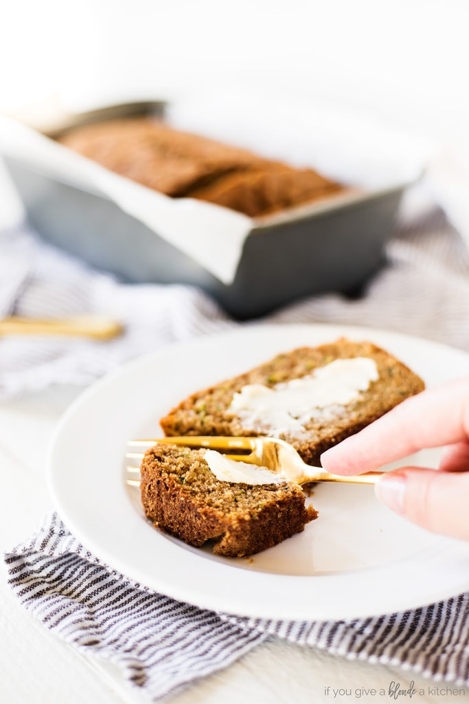 zucchini bread slice on white round plate with butter and gold fork