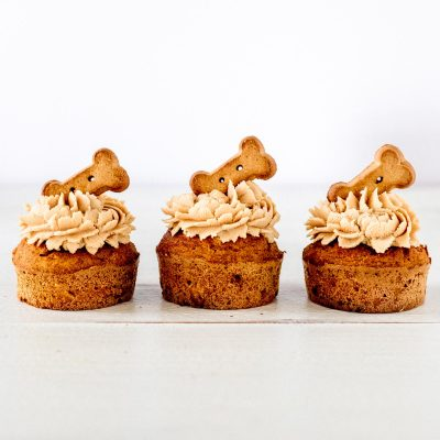 pumpkin peanut butter pupcakes dog biscuits lined up with frosting