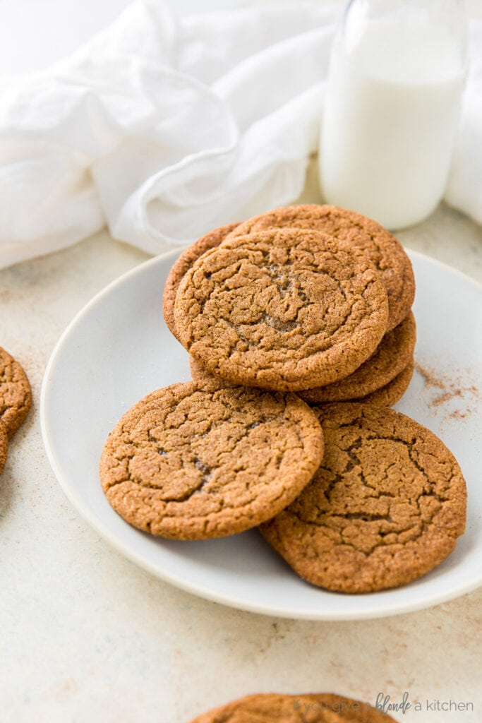 ginger molasses cookies piled on plate with white kitchen cloth and milk bottle behind plate
