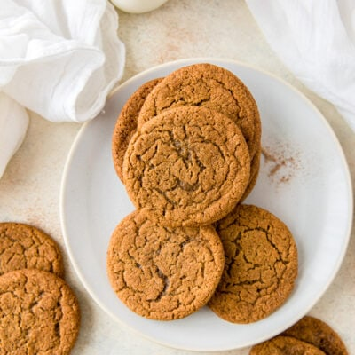plate of ginger molasses cookies with a couple cookies next to plate with milk bottle
