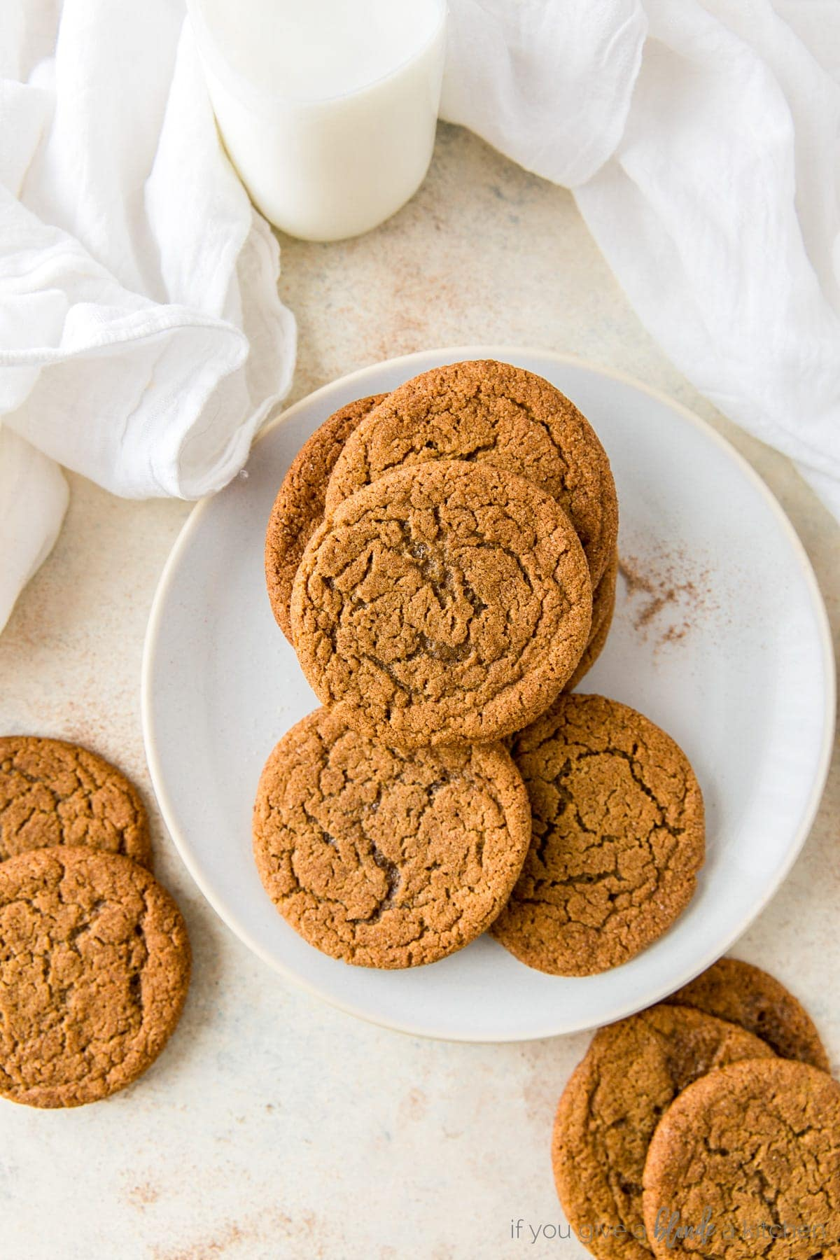 Chewy ginger molasses cookies on cooling rack with kitchen cloth