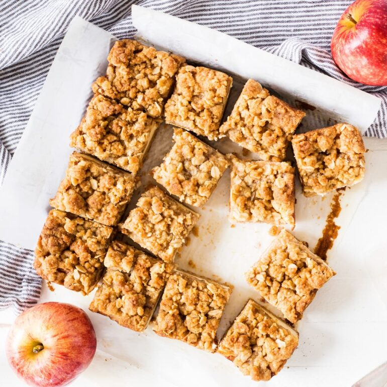 apple cheesecake cut into bars on parchment paper