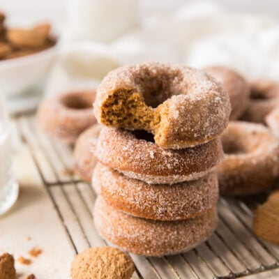 Stack of four gingerbread donuts on wire rack; top donut with a bite taken out